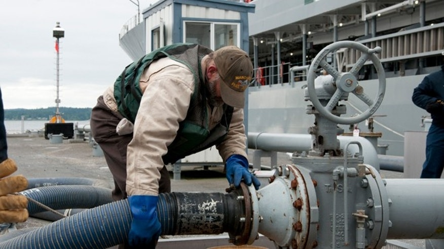 June 13, 2012. A  Navy fuell specialist David Riggs secures a  hose during a biofuels transfer to oiler USNS Henry J. Kaiser.