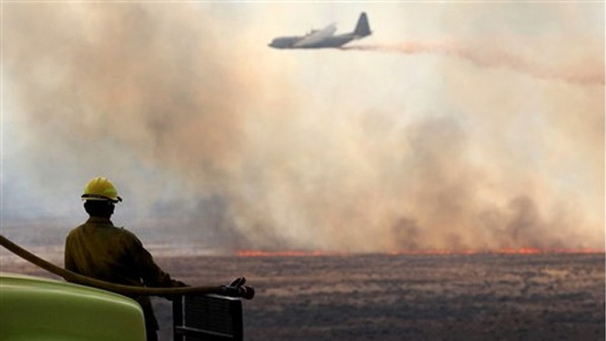 Tuesday, July 10, 2012: Luke Fuller, with Salmon Track Rural Fire District, watches an air tanker drop retardant on a wildfire north of Jackpot, Nev.