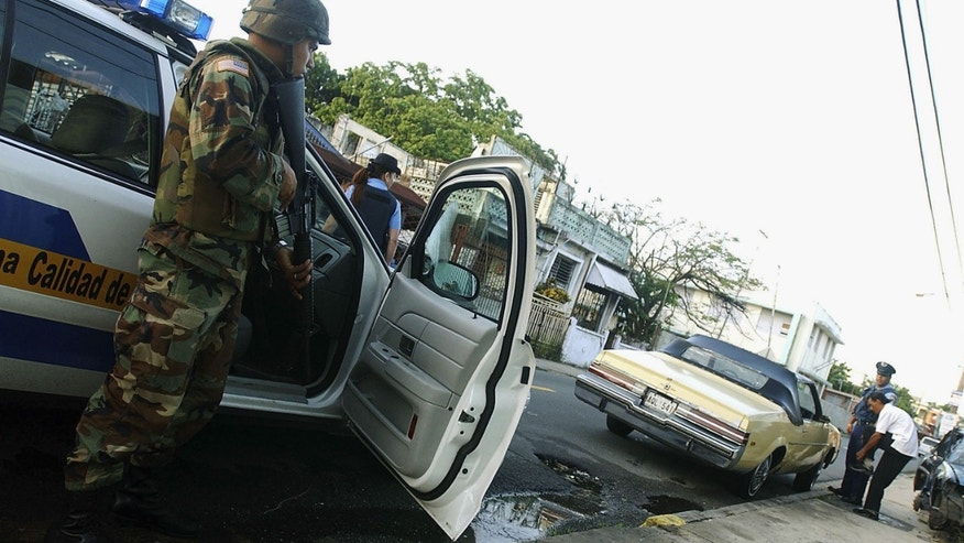 SAN JUAN, PUERTO RICO - JULY 23:  U.S. Army Specialist Michael Montijo joins Puerto Rico Police Department officers on an early morning patrol July 23, 2004 in San Juan, Puerto Rico. Puerto Rico Governor Sila Maria Calderon activated 500 National Guardsmen to try to bring stability after a crime wave swept the island. (Photo by Jose Jimenez/Getty Images)