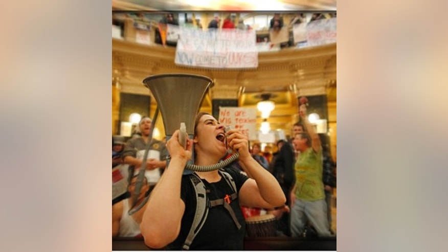 FILE: Feb. 21, 201:  Protesters bang drums and shout slogans inside the state capitol in Madison, Wis.
