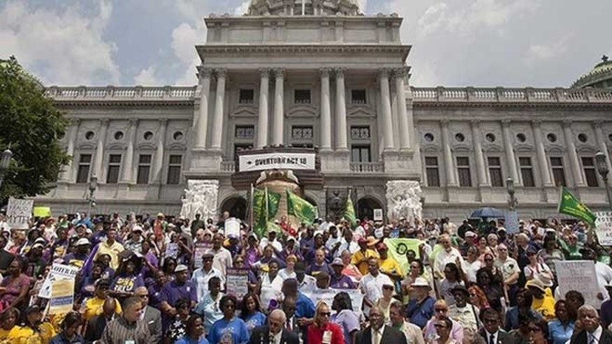 July 24, 2012: Bishop A.E. Sullivan, President of the Interdenominational Ministers Conference, bottom center, speaks during the NAACP Voter ID rally in front of the Pennsylvania State Capitol.