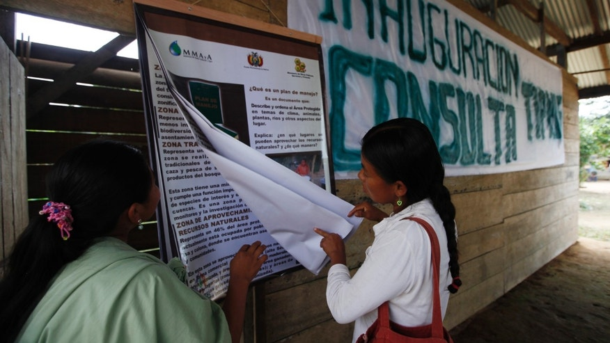 People read information before voting in a referendum in San Miguelito, part of the TIPNIS reserve, Bolivia, on Sunday. (AP Photo/Juan Karita)