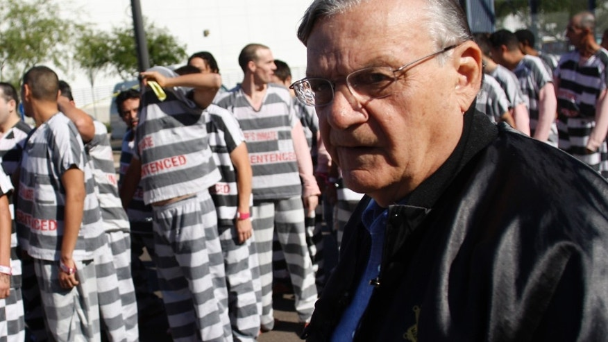 PHOENIX, AZ - APRIL 17:   Inmates walk as they are moved after being ordered by Maricopa County Sheriff Officer Joe Arpaio (R), looking on, to be placed into new housing to open up new beds for maximum security inmates on April 17, 2009 in Phoenix, Arizona. Arpaio has been facing criticism from Hispanic activists and lawmakers, alleging that Arpaio's crackdown methods on illegal immigrants involve racial profiling. (Photo by Joshua Lott/Getty Images) *** Local Caption *** Joe Arpaio