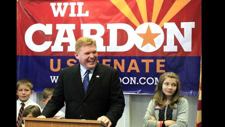 Mesa, Ariz. businessman Wil Cardon, center, flanked by two of his five children, Rebecca Cardon, 11, right, and Parley Cardon, 10, is seen here as he begins his U.S. Senate statewide campaign in Phoenix. Now he is backing off his criticism of his opponent, Rep. Jeff Flake, who is the frontrunner.