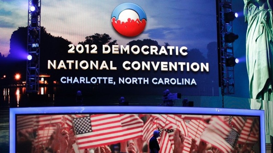 A worker crosses the main stage at Time Warner Cable Arena during the public unveiling of Democratic National Convention's facilities in Charlotte, N.C., Friday, Aug. 31, 2012. (AP Photo/Chuck Burton)