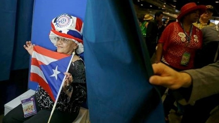 Sept. 5, 2012: New York delegate Julia Rodriguez poses with a Puerto RIco flag in Charlotte, N.C.