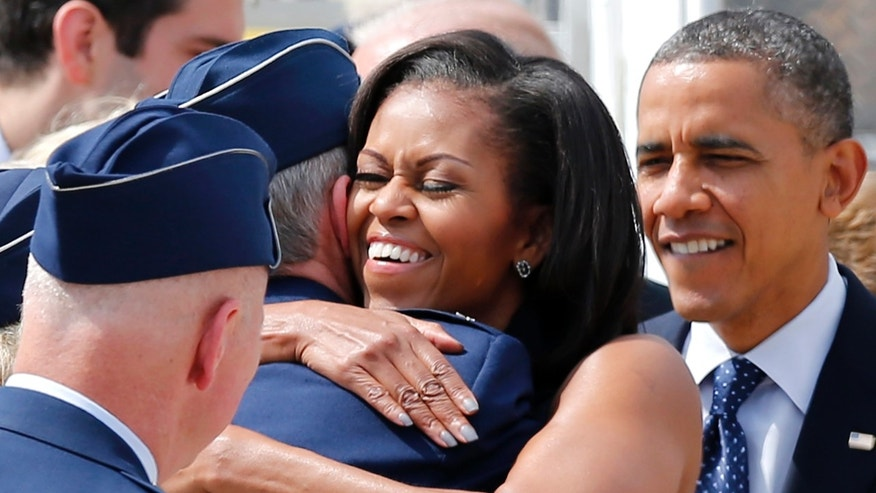 Sept. 7, 2012: President Barack Obama watches as his wife, first lady Michelle Obama, greets service members upon their arrival at Pease Air National Guard Base in Portsmouth, N.H.