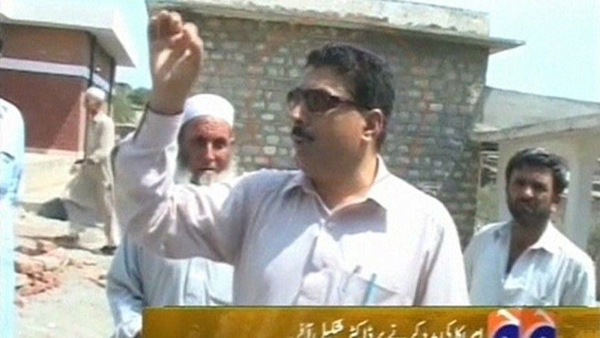 Pakistani doctor Shakil Afridi talks with people outside a building at an unknown location in Pakistan in this still image taken from file footage released May 23, 2012.