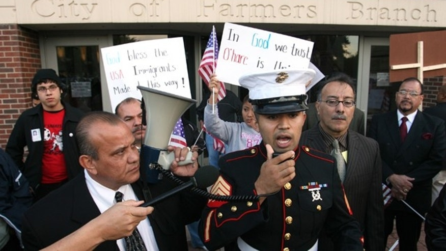 Nov. 13, 2006: FILE photo, former Marine Sgt. Salvadaor Parada, right, speaks to protesters during a rally outside city hall in Farmers Branch, Texas.  A federal appeals court will review Farmers Branch's ordinance, which allows the city building inspector to evict any undocumented immigrant renters.