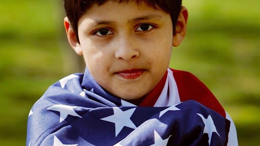 WASHINGTON - APRIL 10:  Eight-year-old Marlon Delgado is wrapped in a U.S. flag.  (Getty Images)