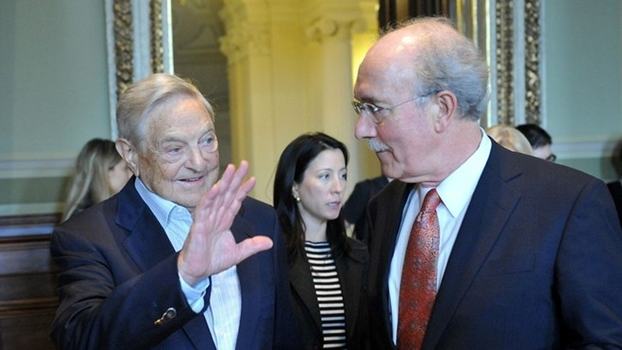 Sept. 14, 2012: Hungarian born US billionaire philanthropist and Honorary Chairman of Board of Trustees of Central European University George Soros, left, waves as he arrives with President and Rector of CEU John Shattuck, right, for the ceremonial opening of the new academic year of the university in the session hall of the Hungarian Academy of Sciences in Budapest, Hungary.