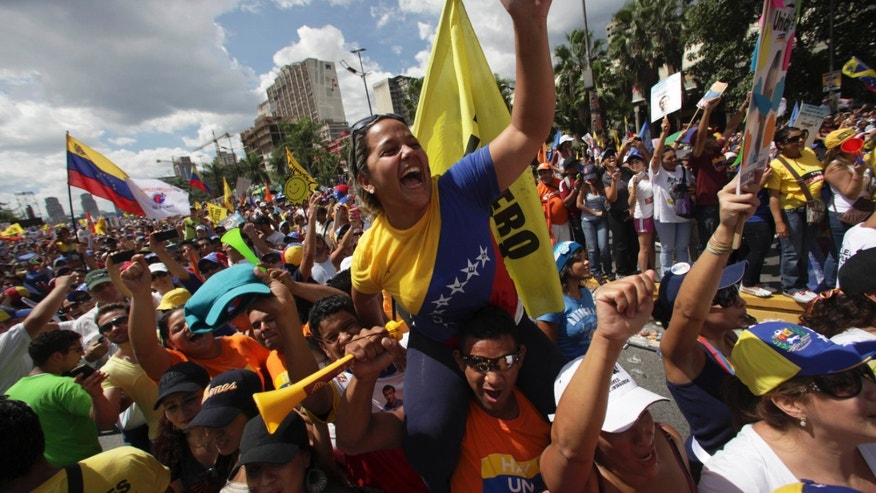Supporters of opposition presidential candidate Henrique Capriles cheer during a campaign rally in Caracas, Venezuela, Sunday, Sept. 30, 2012. (AP Photo/Fernando Llano)