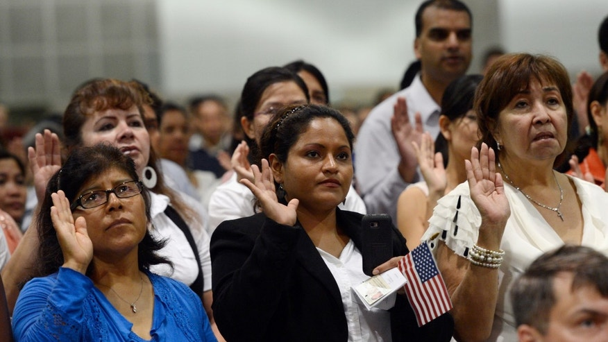LOS ANGELES, CA - AUGUST 23:  U.S. citizenship candidates take the oath of citizenship at a naturalization ceremony at the Los Angeles Convention Center on August 23, 2012 in Los Angeles, California. Nearly 7,800 candidates became citizens representing more than 100 countries.  (Photo by Kevork Djansezian/Getty Images)
