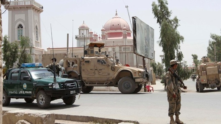 July 14: Afghan and U.S forces stand outside the mosque after a suicide attack in Kandahar, Afghanistan.