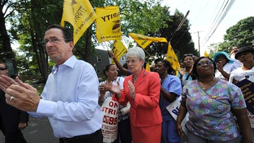FILE: July 11, 2012: Conn. Gov. Dannel P. Malloy and Lt. Gov. Nancy Wyman with striking nursing home workers at a facility in Newington, Conn.
