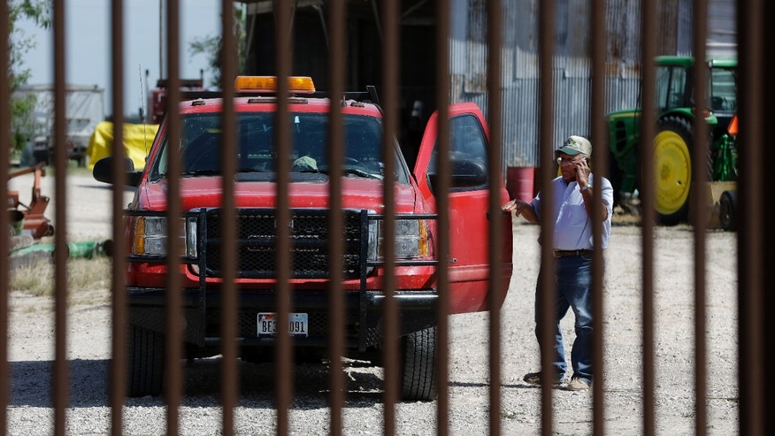 "Sept. 6, 2012: Cotton farmer Teofilo ""Junior"" Flores stands on one side of the U.S.-Mexico border fence that passes across his property in Brownsville, Texas."