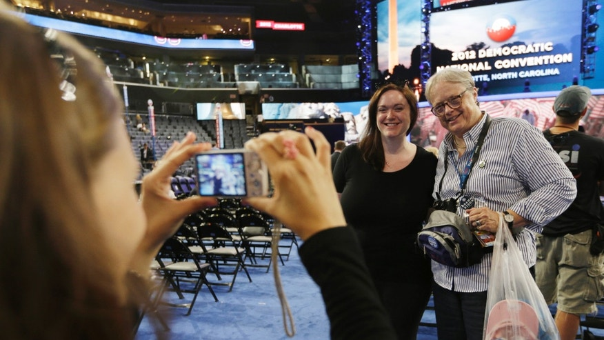 Sept. 2, 2012: Page Fauna Hurley, left, from Burlington, Vt., takes a picture of Julia Barnes, executive director of Vermont Democratic party, and Dottie Deans, right, vice chair of Democratic party from North Pomfret, Vt., on the floor at the Democratic National Convention in Charlotte, N.C.