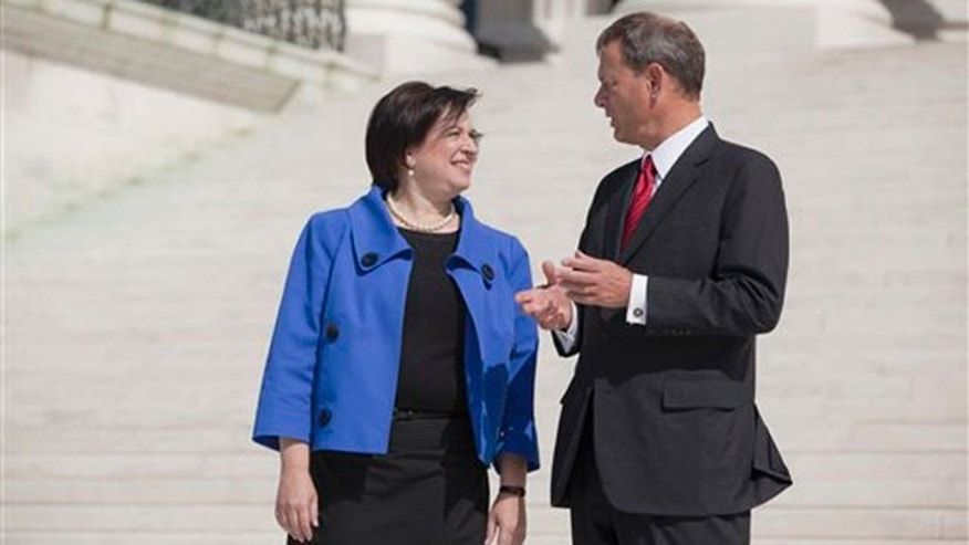 Chief Justice John Roberts and Justice Elena Kagan stand for photographs Oct. 1 at the Supreme Court in Washington. (AP Photo)