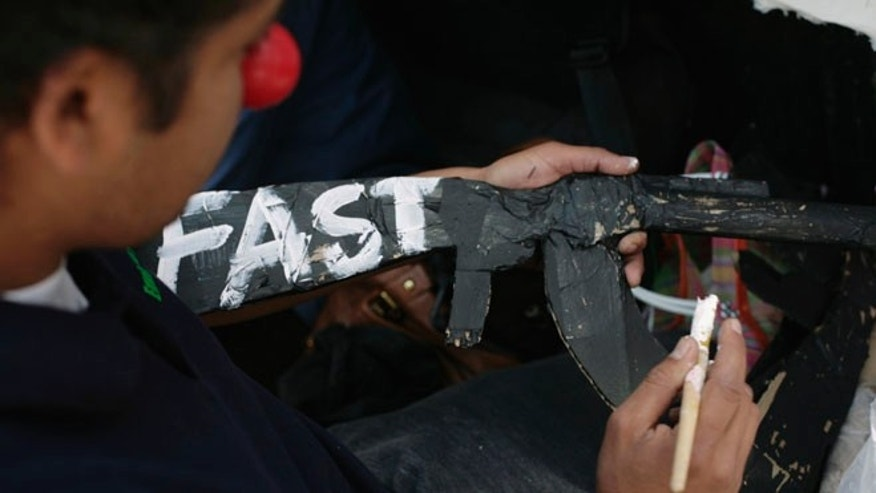 "FILE: October 14, 2011: A man writes ""Fast"" -- in reference to Operation Fast and Furious -- on a paper mache gun during a protest in Mexico City ."