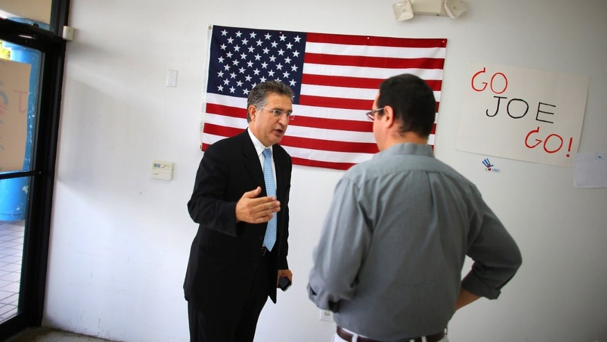 Joe Garcia (L) talks with his campaign manager, John Estes. He defeated opponent Rep. David Rivera (R-FL) in Miami, Florida.