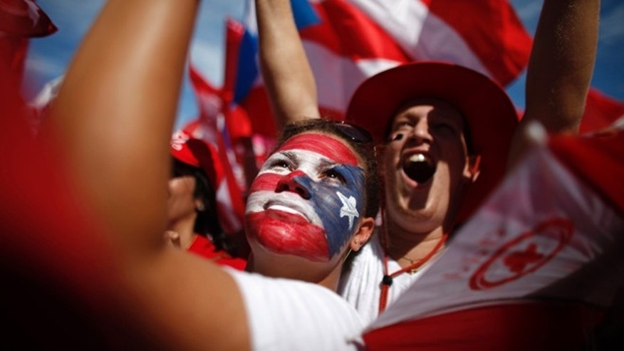 Supporters of Alejandro Garcia Padilla, candidate for governor of the pro-commonwealth Popular Democratic Party, cheer during his closing campaign rally in San Juan, Puerto Rico, Sunday, Nov. 4, 2012.