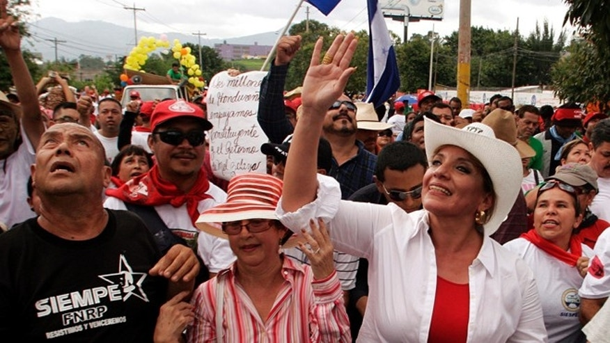 FILE - In this May 1, 2010 file photo, Xiomara Castro Zelaya, right, wife of former Honduras President Manuel Zelaya, waves to supporters during a Labor Day rally in Tegucigalpa, Honduras. The political parties of Honduras are holding primary elections on Sunday, Nov. 18, 2012, as Castro's newly created party, the Libre, or Free party, is trying to break the country's 114- year-old two party system. (AP Photo/Fernando Antonio, file)