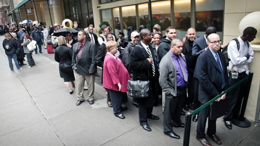 FILE: Oct. 24, 2012: Job seekers wait in line to see employers at a National Career Fairs' job fair in New York.