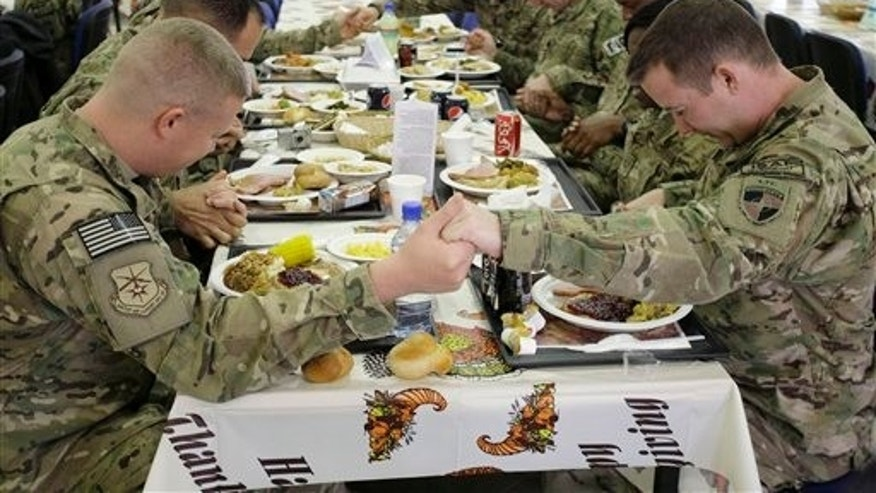 Nov. 22, 2012: U.S. soldiers pray before eating a Thanksgiving meal at a dining hall at the U.S.-led coalition base in Kabul, Afghanistan.
