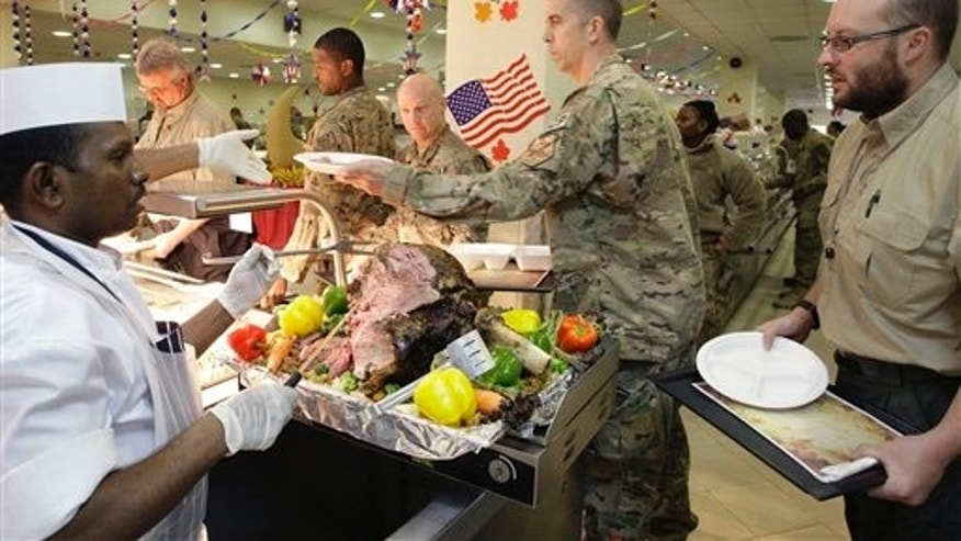 Nov. 22, 2012: A dining facility worker, left, serves meat to soldiers and civilians for their Thanksgiving meal at the U.S.-led coalition base in Kabul, Afghanistan. The dining hall at the U.S.-led coalition base in the Afghan capital served up mac-and-cheese along with traditional Thanksgiving Day fixings.