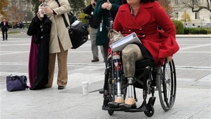 Nov. 15, 2012: Duckworth, an Iraq War veteran who lost both legs in combat before turning to politics, arrives for a group photo on the East steps of the Capitol in Washington.