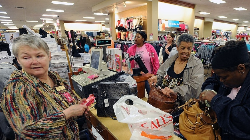 FILE: Thursday, Nov. 22, 2012: Linda Robinson runs the register for shoppers Maxine Rocquemore, center, and Romona Rocquemore at the Bealls Department Store in Nacogdoches, Texas.