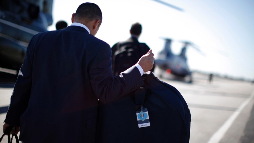 FILE: February 16, 2012.  A White House staffer carries a suit bag labelled for President Obama at John Wayne Airport in Orange County, Calif.