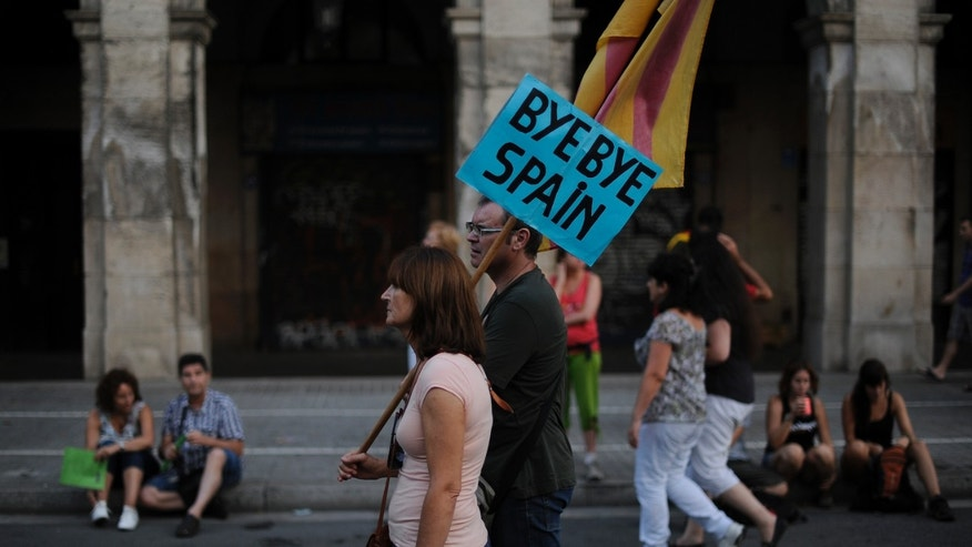 BARCELONA, SPAIN - SEPTEMBER 11:  A couple holds a banner that reads 'Bye Bye Spain' during a demonstration calling for independence during the Catalonia's National Day on September 11, 2012 in Barcelona, Spain. Thousands of Catalans took to the streets of Barcelona demanding a split from Spain and control of their own economy under the slogan 'Catalonia: New European State' on Catalonia's National Day. The Diada Nacional is held every September 11 to remember the defeat of the Catalan troops in 1714.  (Photo by David Ramos/Getty Images)