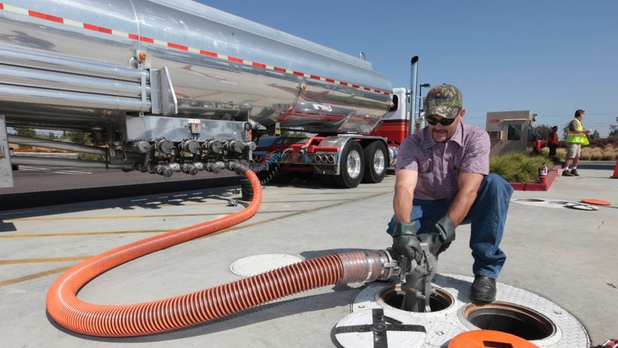 FILE: Thursday, Oct. 4, 2012: Lee Huffman removes a gas hose after delivering gas to the Costco gas station in Lodi, Calif.