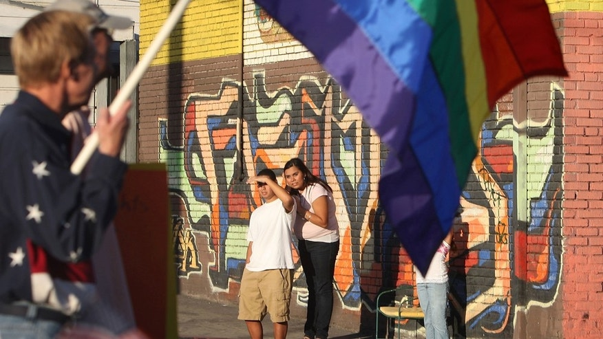 LOS ANGELES, CA -Bystanders on Main Street watch as supporters of same-sex marriage organized by Latino activists march between predominantly Latino neighborhoods on the Eastside and downtown to overturn Proposition 8.