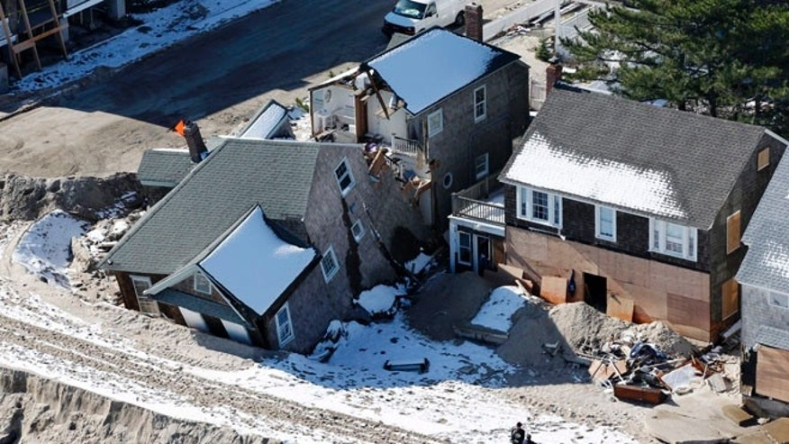 Nov. 9, 2012: In this aerial file photo, people stand near damaged homes along the Atlantic Ocean in New Jersey after the region was pounded by Superstorm Sandy.