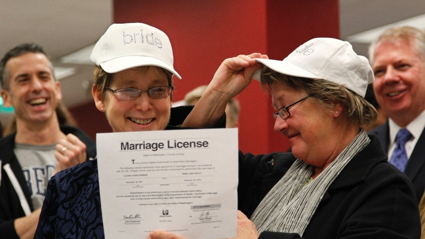 "Dec. 6, 2012: Claudia Gorbman, left, and partner Pam Keeley wear caps both reading ""bride"" as they display their newly-issued marriage license."