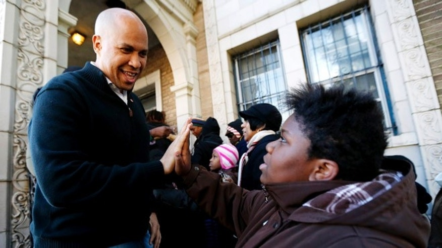Nov. 9, 2012: Newark Mayor Cory Booker, left, greets 13-year-old Blonbzell Taylor outside of Clinton Hill Community Resource Center, where residents impacted by Superstorm Sandy received clothing donations in Newark, N.J.