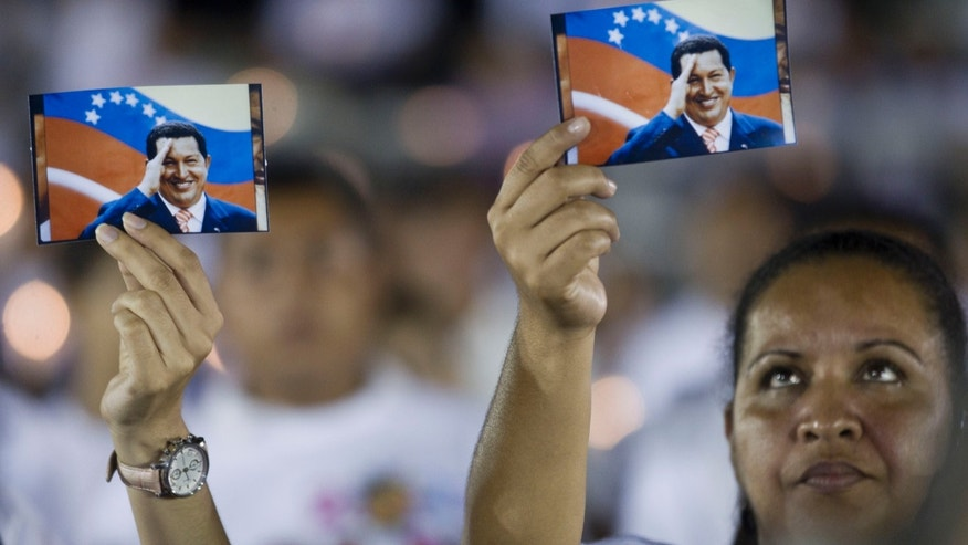 "Supporters of the Venezuela's President Hugo Chavez hold his picture during a vigil in Managua, Nicaragua, Sunday Dec. 9, 2012. Chavez is to return to Cuba Sunday for another surgery in his battle against cancer, which has led him to speak publicly of a successor for the first time. Chavez said Saturday that if there are ""circumstances that prevent me from exercising the presidency further"" Vice-President Nicolas Maduro should replace him for the remainder of his term.(AP Photo/Esteban Felix)"