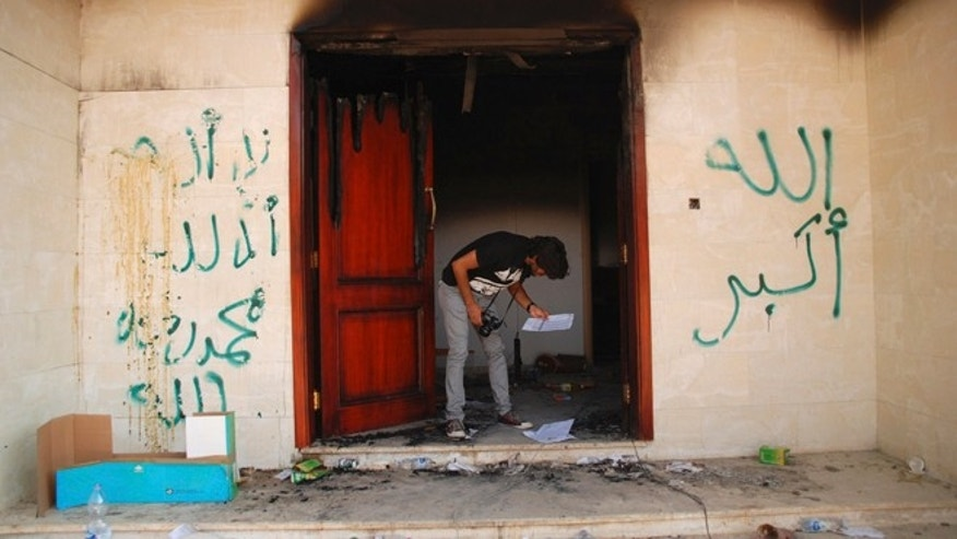 Sept. 12, 2012: In this file photo, a man looks at documents at the U.S. consulate in Benghazi, Libya, after an attack that killed four Americans, including Ambassador Chris Stevens.