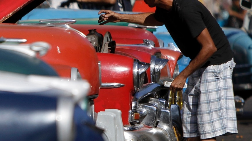 A man repairs a classic American car that is used as a taxi in Havana, Cuba.