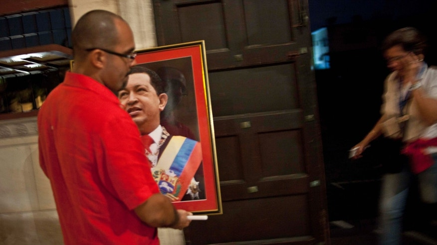 A man carries an image of Venezuela's President Hugo Chavez after a mass in support of him in Havana, Cuba, Thursday, Dec. 13, 2012. Chavez is recovering favorably despite suffering complications during cancer surgery in Cuba, his vice president Nicolas Maduro said Thursday amid uncertainty over the Venezuelan leader's health crisis and the country's political future. (AP Photo/Ramon Espinosa)