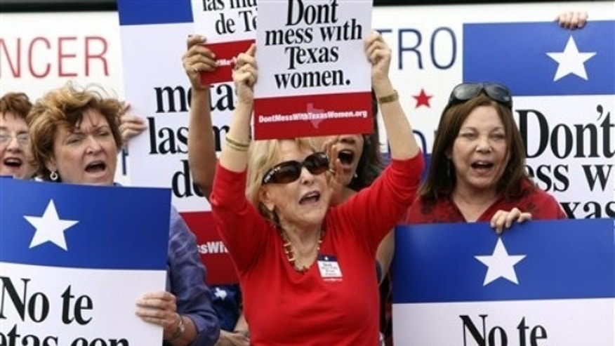 March 6, 2012: Mary Green, Peg Armstrong and Jan Perrault hold up signs during Women's Health Express, a bus event held in San Antonio, Texas, to protest the attempt to cut Planned Parenthood out of the state's Women's Health Plan.