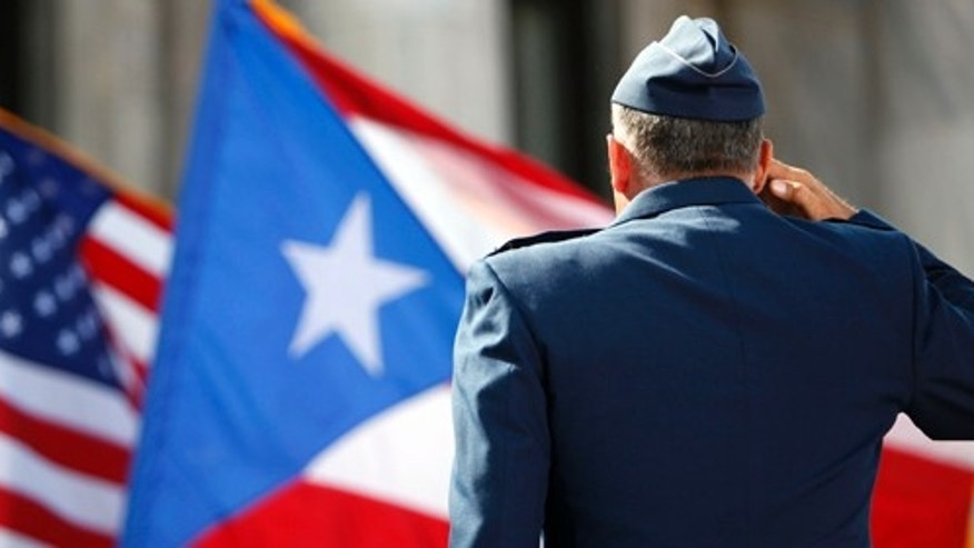 A member of the U.S. Army Honor Guard salutes the Puerto Rican and U.S. flags during the inaugural ceremony for governor-elect Alejandro Garcia Padilla, at the Capitol building in San Juan, Puerto Rico, Wednesday, Jan. 2, 2013. Garcia is a 41-year-old attorney and former local senator who narrowly defeated pro-statehood Gov. Luis Fortuno. He was sworn in on a stage overlooking the Atlantic Ocean amid the cheers of thousands of supporters from his party, which opposes statehood. (AP Photo/Ricardo Arduengo)