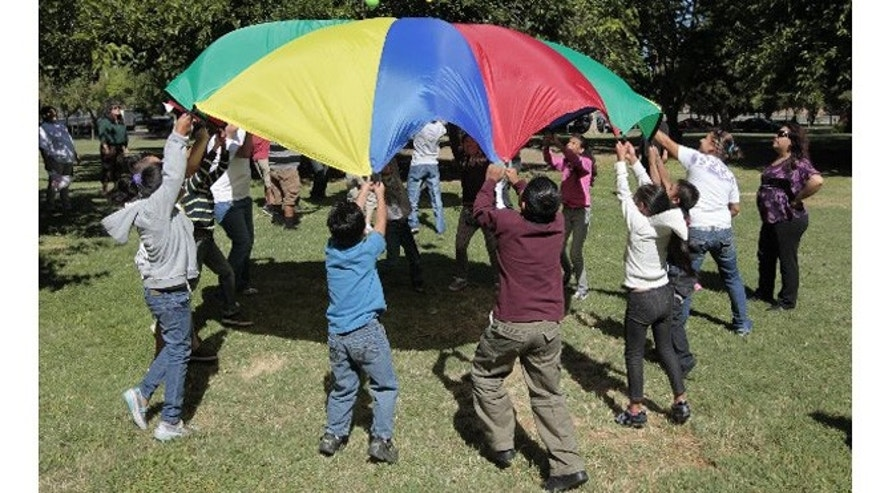Children and adults uses a play parachute as past of an exercise activity during a wellness program run jointly by the La Familia Counseling Center and the YMCA in Sacramento. The program is funded by 2004's Proposition 63. A fifth of the revenue from the measure goes to activities, like wellness programs. (AP Photo/Rich Pedroncelli)