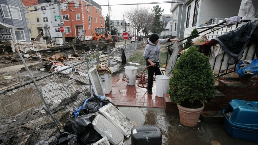 FILE: Nov. 1, 2012: Ruth Dina Ticona washes the mud from clothing damaged by Superstorm Sandy in the front yard of her home in the oceanside community of Far Rockaway, New York, N.Y.