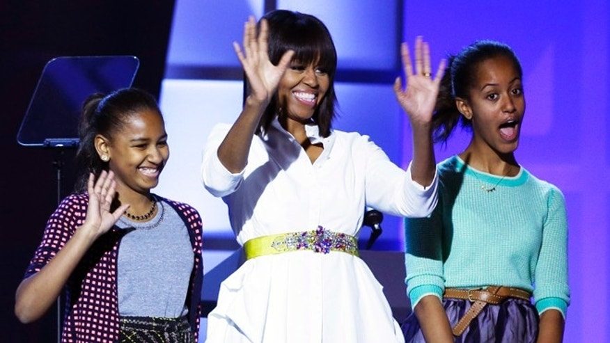 "Jan. 19, 2013: First lady Michelle Obama, center, and daughters Sasha, left, and Malia, right, react during the Kids' Inaugural: Our Children. Our Future."" event in Washington, as part of the 57th Inauguration weekend of events."