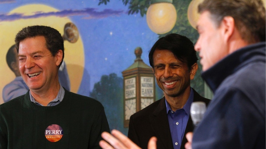 FILE: January 2, 2012: Kansas Gov. Sam Brownback (L), Louisiana Governor Bobby Jindal (C) and then-GOP presidential candidate and Texas Gov. Rick Perry in Perry, Iowa.
