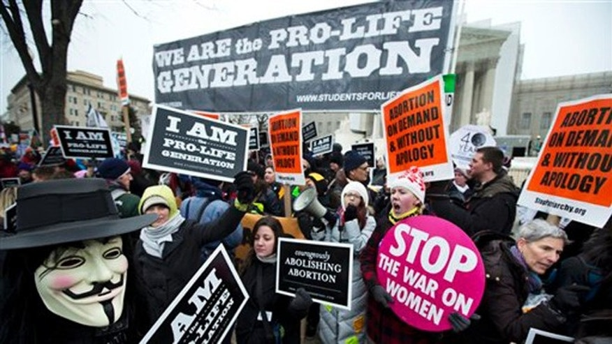 Pro-abortion rights activists, rally face-to-face against anti-abortion demonstrators as both march in front of the U.S. Supreme Court in Washington, Friday, Jan. 25, 2013, in a demonstration that coincides with the 40th anniversary of the Roe vs. Wade decision that legalized abortion. (AP Photo/Manuel Balce Ceneta)