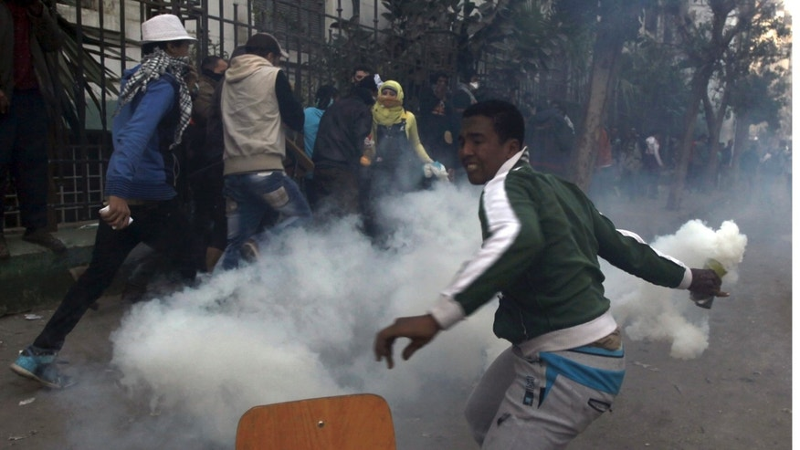 Saturday, January 26, 2013: A protester opposing Egyptian President Mohamed Morsi throws a tear gas canister along Mohamed Mahmoud Street, which leads to the Interior Ministry, near Tahrir Square in Cairo.